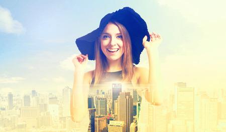 exposicion: Doble exposición de una mujer joven feliz en un sombrero y un gran horizonte de la ciudad