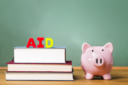 textbooks: Student aid theme with textbooks and piggy bank and chalkboard background