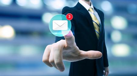correo electronico: Empresario apuntando a un icono de correo electr�nico en el fondo borrosa ciudad
