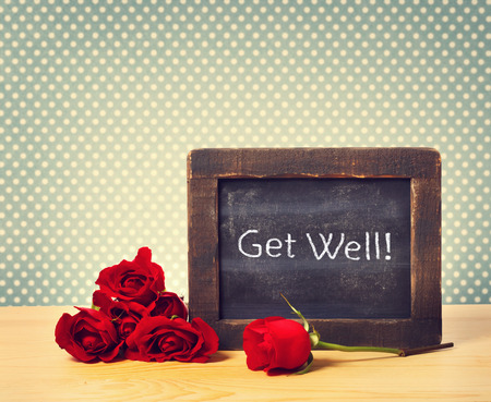get well: Close up Get Well Text on a Small Chalkboard with Fresh Red Roses on an a Polka Dots Background Stock Photo