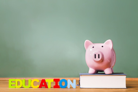 Education theme with textbooks and piggy bank and green chalkboard background Stock Photo
