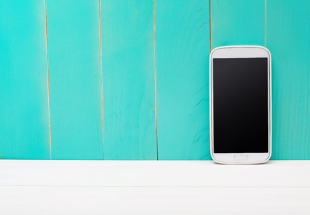 handphone: White smart phone on teal wooden background
