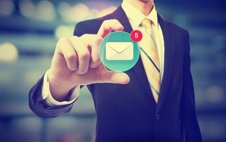 personen: Bedrijfs mens die een e-pictogram op wazig stadsgezicht achtergrond Stockfoto