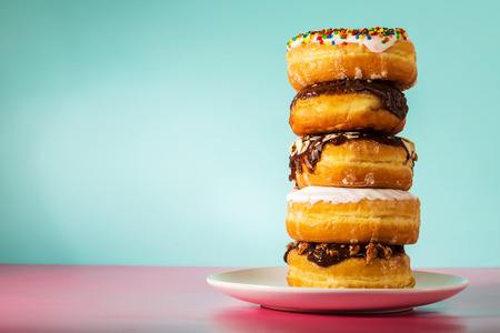Stack of assorted donuts on a white plate on pastel blue and pink background