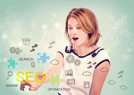 Mooie jonge vrouw het activeren van een SEO-interface op het virtueel scherm met verspreide SEO iconen voor het optimaliseren van een website Stockfoto
