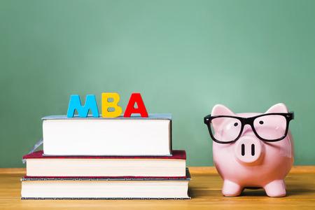 economia aziendale: Master of Business Administration tema con libri di testo e il porcellino salvadanaio e lavagna verde