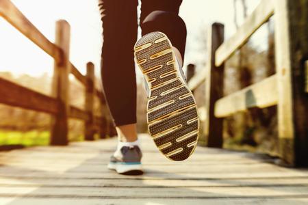 personas trotando: Mujer joven que activa a través de un puente viejo país al atardecer Foto de archivo