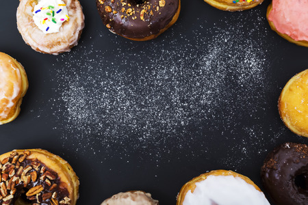 Assorted donuts with powder flour on black background
