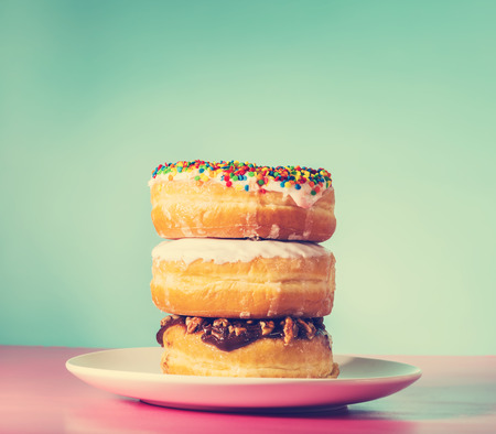 dessert plate: Stack of assorted donuts on a white plate on pastel blue and pink background