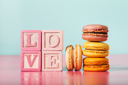 Macarons with LOVE message on wooden blocks on pastel pink and blue background Stock Photo