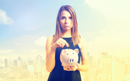 depositing: Unhappy young woman depositing money into her pink piggy bank