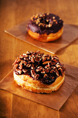 Chocolate pecan donuts on rustic wooden table