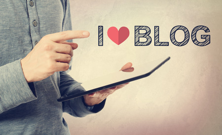 young man: Young man pointing at I love Blog text over a tablet computer Stock Photo