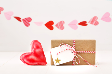 giftwrapped: A garland of hearts above a small gift-wrapped box and red textile heart on a neutral white background