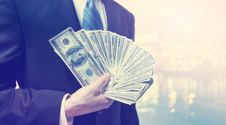 business money: Businessman displaying spread of cash on blurred light background
