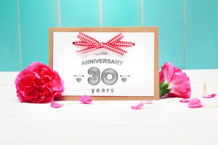 aniversario de boda: 30 aniversario tarjeta de mensajes hechos a mano de celebración con claveles Foto de archivo