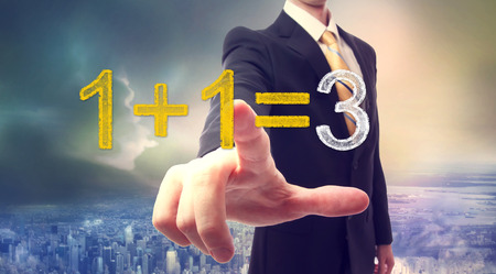 synergy: Businessman pointing at synergy concept 1+1=3 above the city Stock Photo