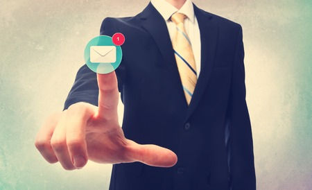 Business man pressing an email button on a blurred neutral background