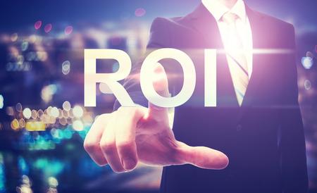 rendement: Zakenman die op de ROI (return on investment) op onscherpe achtergrond van de stad