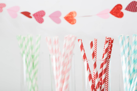 compleanno: Colorful paper straws with a decorative garland of hearts symbolic of love to celebrate a party for a festive romantic occasion