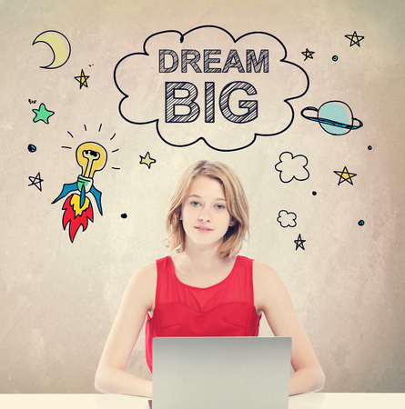 Dream Big concept with young woman working on a laptop