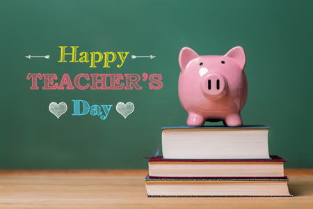 Happy Teachers Day message with pink piggy bank on top of books