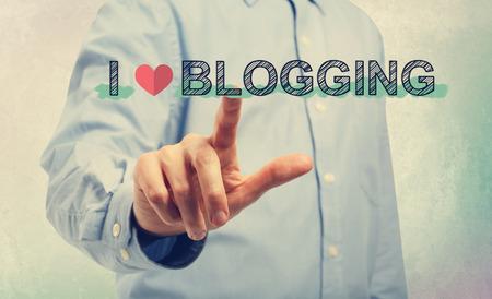 hombre escribiendo: Hombre joven en camisa azul que señala en Amo el Blogging