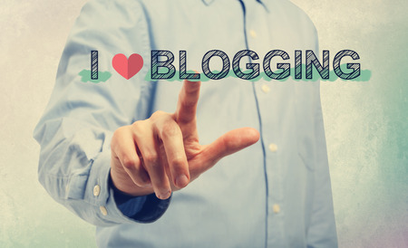 design media love: Young man in blue shirt pointing at I Love Blogging Stock Photo