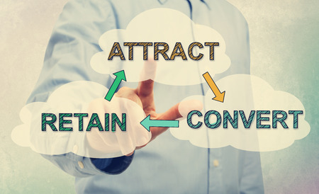convert: Young man in blue shirt pointing at Attract, Convert and Retain texts Stock Photo