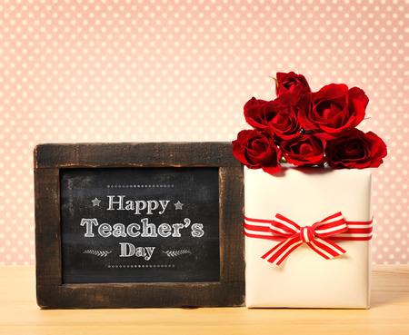 profesores: Mensaje feliz Día del Maestro en la pequeña pizarra con caja de regalo y rosas rojas Foto de archivo