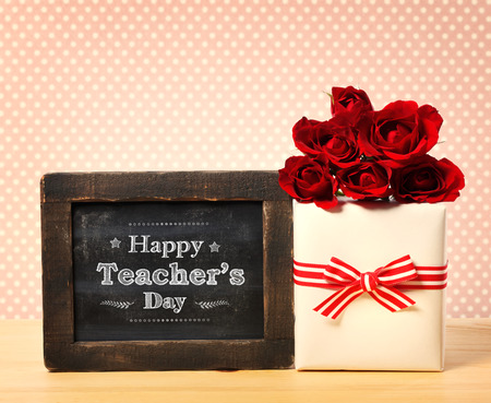 Happy Teachers Day message on small chalkboard with gift box and red roses