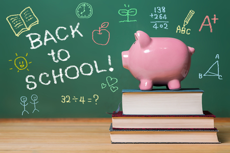 studying classroom: Back to School message with pink piggy bank on top of books with chalkboard Stock Photo
