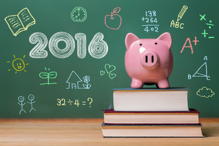 text books: Year 2016 text with pink piggy bank on top of books with chalkboard Stock Photo