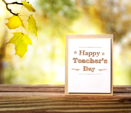 Happy Teachers Day greeting card on shinning fall background