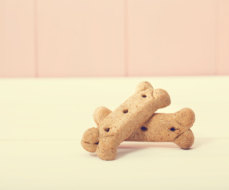 biscuits: Bone shaped dog treats on pink wooden wall