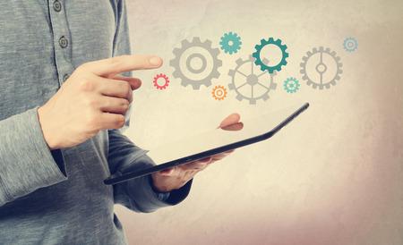 カラフルな歯車でタブレット コンピューターを指している若い男
