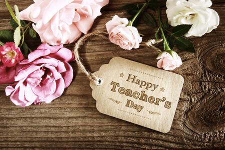 maestro: Tarjeta feliz del mensaje Día del Maestro con pequeñas rosas en el fondo de madera