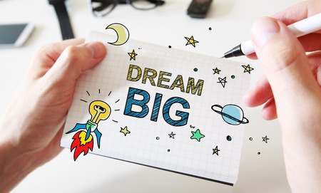 Hand drawing Dream Big concept on white notebook