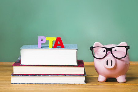 Parent Teacher Association theme with pink piggy bank with chalkboard in the background as concept image of the costs of education