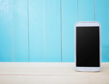 White smart phone on light blue wooden background