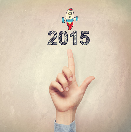 filtered: Hand pointing to 2015 concept on light brown wall background Stock Photo