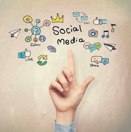friend chart: Hand pointing to Social Media concept on light brown wall background Stock Photo