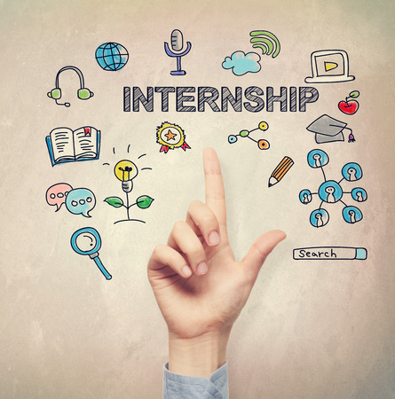 light brown background: Hand pointing to Internship concept on light brown wall background