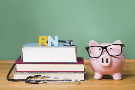 registered nurse: Registered Nurse RN theme with pink piggy bank with chalkboard in the background as concept image of the costs of education