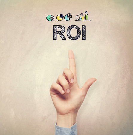filtered: Hand pointing to ROI concept on light brown wall background