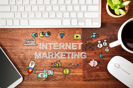 internet marketing: Internet Marketing concept with workstation on a wooden desk