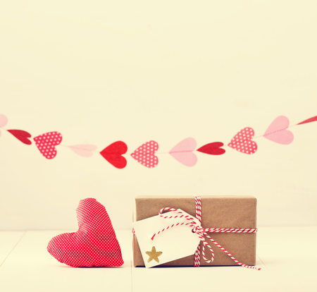 giftwrapped: A garland of hearts above a small gift-wrapped box and red textile heart on a neutral white with copyspace Stock Photo