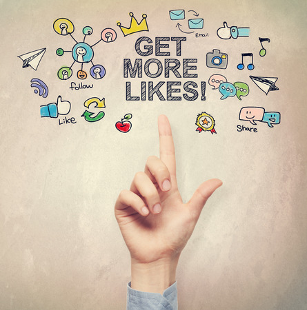 Hand pointing to Get More Likes concept on light brown wall background