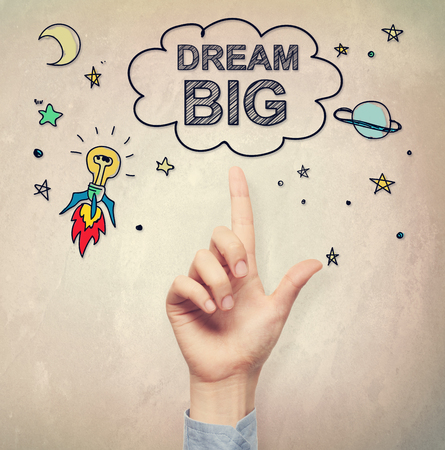 hand pointing: Hand pointing to Big Dream concept on light brown wall