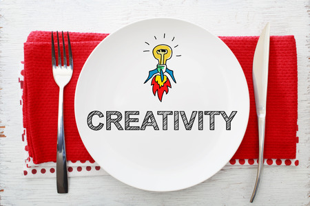 creativity concept: Creativity concept on white plate with fork and knife on red napkins Stock Photo